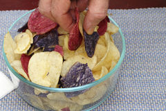 Choosing Red, White and Blue Potato Chips. Fingers grasping red, white and blue potato chips from a bunch in a bowl. Fingers picking up Red Crimson, Purple stock images