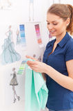 Choosing the right color. Beautiful female fashion designer choosing color of the future dress while standing near the wall with sketches handing on it Royalty Free Stock Images