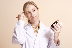 Choosing the right medicine. A female worker holding naturapathic and traditional medications Royalty Free Stock Image