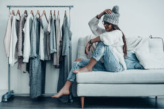 Choosing the right option. Thoughtful young woman in casual wear adjusting her hat and looking away while sitting on the couch at home near her clothes hanging Stock Image
