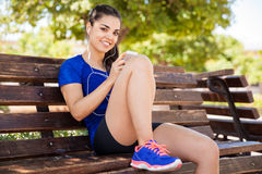 Choosing the right song. Female runner sitting on a park bench and choosing the perfect song for her workout Royalty Free Stock Photo