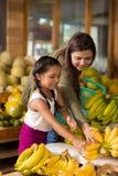 Choosing ripe bananas. Indian mother and daughter choosing ripe bananas at the fruit market Stock Image
