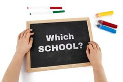 Choosing a school for your child problem depicted. Choosing a school for your child problem depicted with childs hand and chalkboard with text - top view royalty free stock photos