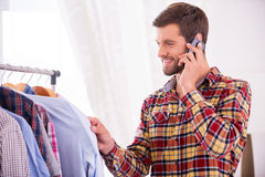 Choosing shirt to wear. Handsome young man choosing shirt to wear and talking on the mobile phone Royalty Free Stock Photos