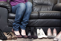 Choosing shoes. A young girl wearing jeans is figuring out which pair of shoes to wear, between seven pairs of shoes that are standing in row in front of a black Royalty Free Stock Photo