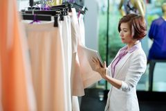 Choosing skirt. Business woman with a digital tablet choosing skirt in a clothing store Royalty Free Stock Images