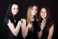 Choosing songs in karaoke. Three beautiful girls in karaoke choosing songs, having fun Royalty Free Stock Photos