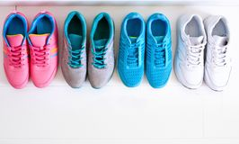 Choosing sports shoes. A sporty girl in jeans chooses which sneakers to go for training. Several pairs of sports shoes and legs Stock Image