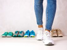 Choosing sports shoes. A sporty girl in jeans chooses which sneakers to go for training. Several pairs of sports shoes and legs Royalty Free Stock Image