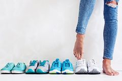 Choosing sports shoes. A sporty girl in jeans chooses which sneakers to go for training. Several pairs of sports shoes and legs Stock Images
