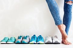 Choosing sports shoes. A sporty girl in jeans chooses which sneakers to go for training. Several pairs of sports shoes and legs Stock Photos