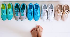 Choosing sports shoes. A sporty girl in jeans chooses which sneakers to go for training. Several pairs of sports shoes and legs Stock Photography