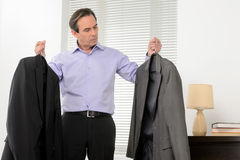 Choosing a suit for meeting. Mature businessman standing with a. Suit in each hand and choosing the best one to wear Stock Image