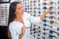 Choosing sunglasses in store. Stock Photography