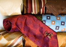 Choosing a tie and cufflinks. Choosing a red tie and gold cufflinks from a selection of colorful neckties in a box Stock Photography