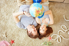 Choosing vacation tour. Restful young couple with globe lying on the floor at home Stock Image
