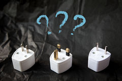 Choosing from various electric plug adapters. Difficulties and problems of traveling Royalty Free Stock Photo