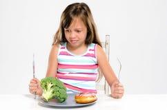 Choosing between vegetable and dessert Royalty Free Stock Image