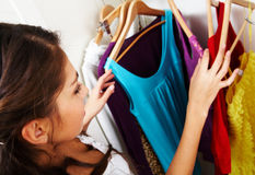 Choosing what to wear. Image of pretty female looking through her wardrobe and choosing smart dress Royalty Free Stock Photos