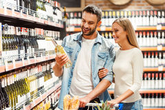 Choosing wine for dinner. Happy young couple choosing wine together while standing in wine store royalty free stock photos