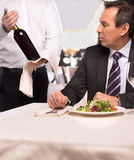 Choosing wine. Sommelier proposing wine to senior men sitting at the restaurant royalty free stock photos