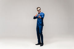 Choosing you. Full length studio shot of handsome young smiling man in full suit and bow tie looking at camera and gesturing Royalty Free Stock Photo