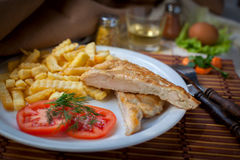 Chop with French fries and tomatoes. Chop and fries with tomatoes on the plate Royalty Free Stock Image