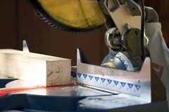Chop saw. Cutting a piece of lumber with a miter or chop saw royalty free stock images