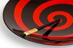 Chop sticks and a bowl. Two chop sticks on a beautiful black and red bowl Royalty Free Stock Images