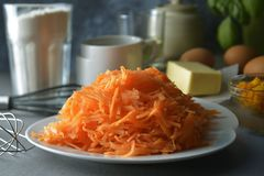 Choped carrots for carrot cake, pie or muffins. Ingredients for cooking carrot pie or cake. Cooking dessert. Carrots for carrot cake, pie or muffins. Ingredients stock images