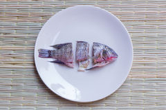 Choped fish. Small choped fish in round dish,  on a traditional mat Royalty Free Stock Image