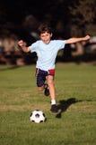 Chłopiec bawić się piłkę nożną w parku Obrazy Royalty Free