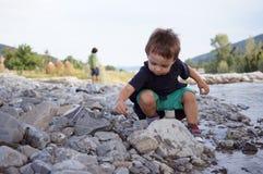 Chłopiec bawić się skały i rzuca przy rzeką Obrazy Stock