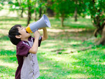Chłopiec chwyta megafon krzyczy w parku Fotografia Stock