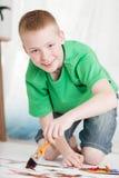 Chłopiec klęczenie na obrazie podczas gdy trzymający muśnięcie Zdjęcia Stock