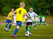 Chłopiec kopie piłki nożnej piłkę Dziecko piłki nożnej drużyna Dzieciaki Biega z piłką na Futbolowej smole Młodzi gracze piłki no Obrazy Royalty Free