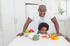 Chłopiec kucharstwo z jego ojcem Fotografia Royalty Free