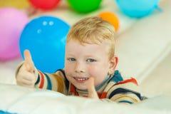 Chłopiec lying on the beach na podłoga otaczającej colourful balonami Zdjęcia Royalty Free