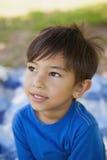 Chłopiec patrzeje daleko od w myśli przy parkiem Zdjęcia Stock