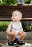 Chłopiec pobliska ławka Zdjęcia Stock