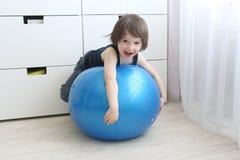 Chłopiec (3 roku) bawić się z dużą błękitną piłką w domu Zdjęcia Royalty Free