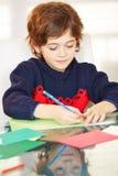 Chłopiec rysunek z piórem przy stołem Zdjęcie Stock