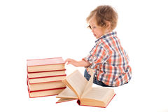 Chłopiec siedzi blisko sterty książki Zdjęcia Stock