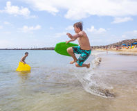 Chłopiec skacze w ocean z jego taniec boogie deską Fotografia Stock