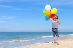 Chłopiec stoi na plaży z balonami Obrazy Stock