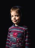 Chłopiec stoi nad czarnym tłem z hoodie Obrazy Stock