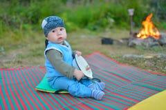 Chłopiec turystyczny obsiadanie na podłoga blisko ogniska i bawić się z łyżką, czeka gdy jedzenie przygotowywa Zdjęcia Royalty Free