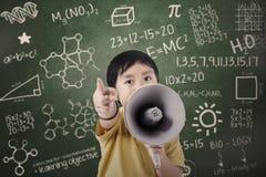 Chłopiec uczeń ogłasza z mówcą przy klasą Obrazy Royalty Free