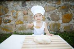 Chłopiec z szefa kuchni kapeluszu kucharstwem Zdjęcie Royalty Free