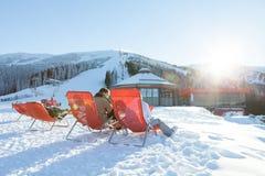 CHOPOK SLOVAKIEN - JANUARI 12, 2017: Skidåkare och snowboarders som att ta vilar i stolar nära apres, skidar stången på sluttande Royaltyfri Bild